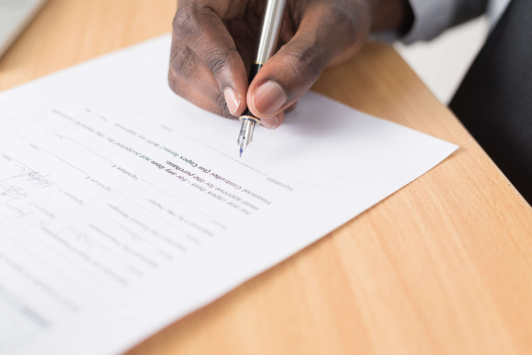 Hand holding a pen and signing a contract